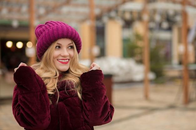 Ehrfürchtig lächelnde blonde frau mit langen üppigen haaren posiert auf der straße in kiew