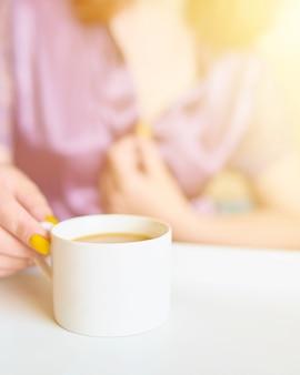 Ehrfürchtige hübsche frau in einem trinkenden kaffee der purpurroten silk robe früh morgens im bett.