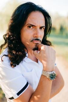 Ehrfürchtiger erwachsener bräunte den sizilianischen mann, der im park aufwirft. italienischer charismatischer kerl mit moderner frisur, bart, schnurrbart im sonnigen park