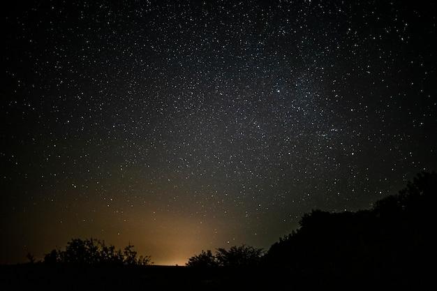 Ehrfürchtiger sternenklarer nächtlicher himmel mit lichtstrahl