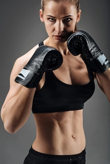 Ehrgeizige frau, die mit boxhandschuhen aufwirft