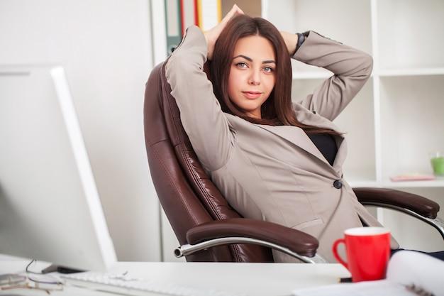 Ehrgeizige geschäftsfrau, die telefonisch am modernen büroarbeitsplatz, kaffee trinkend spricht