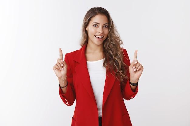 Ehrgeizige gutaussehende frau, die sich fertig macht, wichtige arbeit büropräsentation, die zeigefinger nach oben hebt und den oberen kopienraum zeigt, breit lächeln und sich glücklich fühlen, versichertes erfolgreiches ergebnis interview