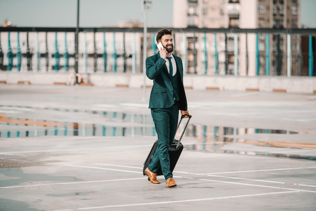 Ehrgeiziger kaukasischer bärtiger geschäftsmann im anzug, der das smartphone benutzt und gepäck trägt, während er auf dem parkplatz aufwacht. geschäftsreisekonzept. hoffe nicht darauf, du musst hart arbeiten, um es zu haben.