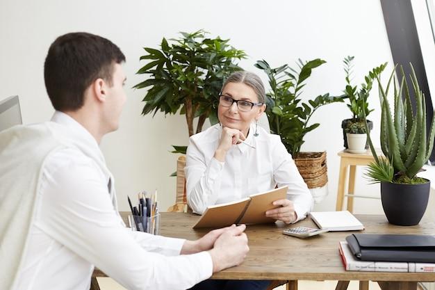 Ehrliche aufnahme eines attraktiven positiven weiblichen ceo mittleren alters in brillen, der notizen im heft macht und talentierten angehenden jungen männlichen jobkandidaten während des interviews in ihrem gemütlichen büro zuhört