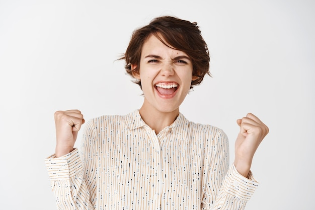 Ehrliches porträt einer glücklichen frau, die den preis gewinnt, sich freut und vor freude ja schreit, die faust pumpen lässt, um den sieg zu feiern, an der weißen wand triumphiert