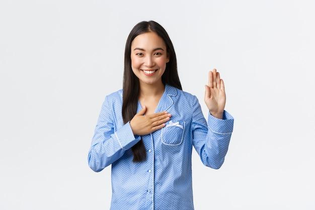 Ehrliches und aufrichtiges schönes asiatisches mädchen im blauen pyjama, das eine hand hebt und handfläche auf herz hält, um versprechen zu machen, wahrheit zu sagen oder eid zu geben, lächelt, als würde es marmeladen über weißer wand tragen