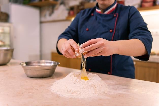 Ei brechen. erfahrener fleißiger koch in der französischen bäckerei, der eier bricht und teig für croissants macht