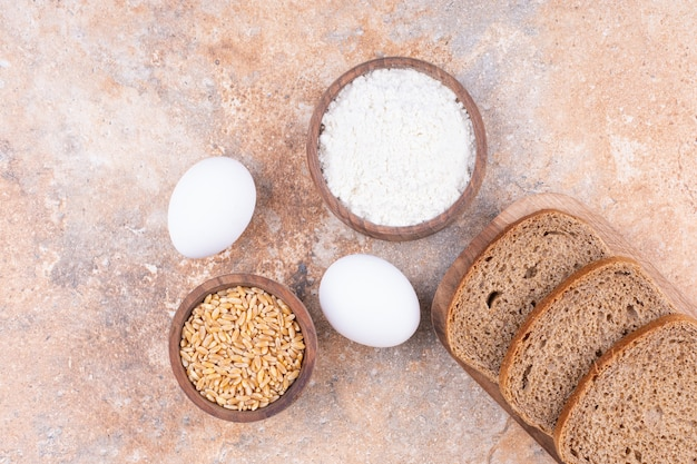 Ei, getreide, mehl und brot in einem holzteller auf dem marmor.