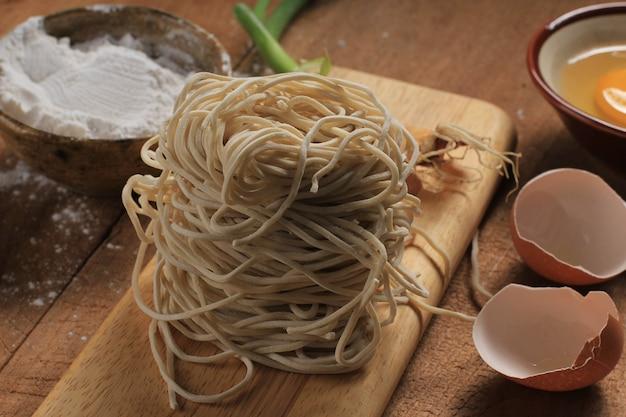 Ei, mehl und rohe asiatische nudeln auf holzbrett