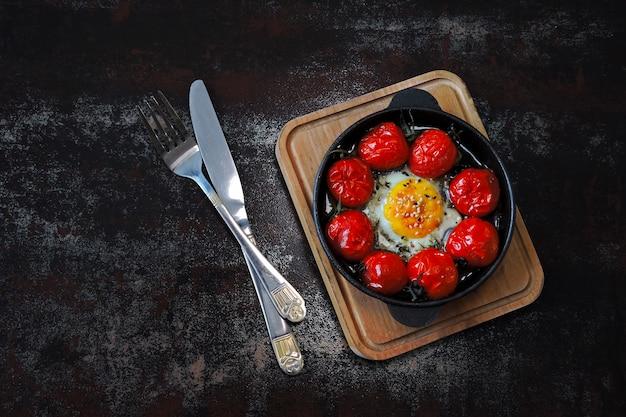 Ei mit kirschtomaten und thymian in einer gusseisernen pfanne gebacken.