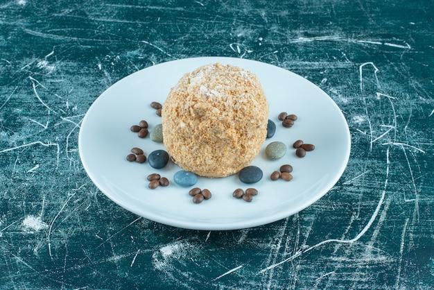 Eichhörnchenkuchen auf einer platte mit süßigkeitensteinen und kaffeebohnen auf blau.