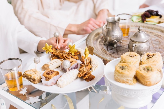 Eid al-fitr konzept mit arabischem essen und freunden