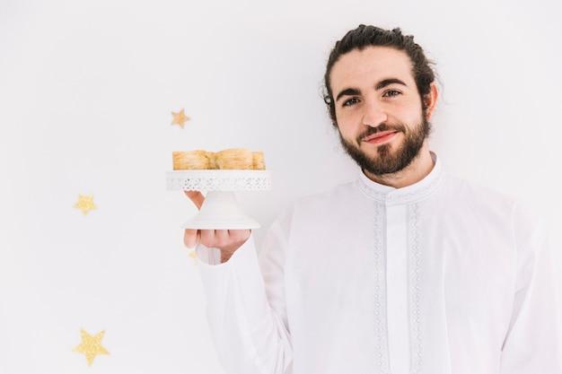 Eid al-fitr konzept mit dem mann, der arabisches gebäck darstellt
