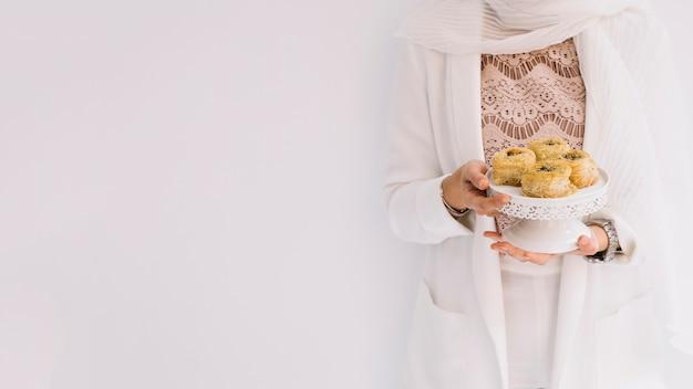 Eid-konzept mit der frau, die arabisches gebäck hält