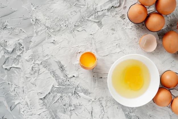 Eier auf dem tisch mit geknacktem in einem halben, eigelb und protein in geöffnetem ei, rühreikochen