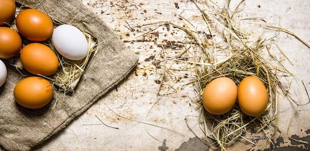 Eier auf der alten tasche und auf dem heu