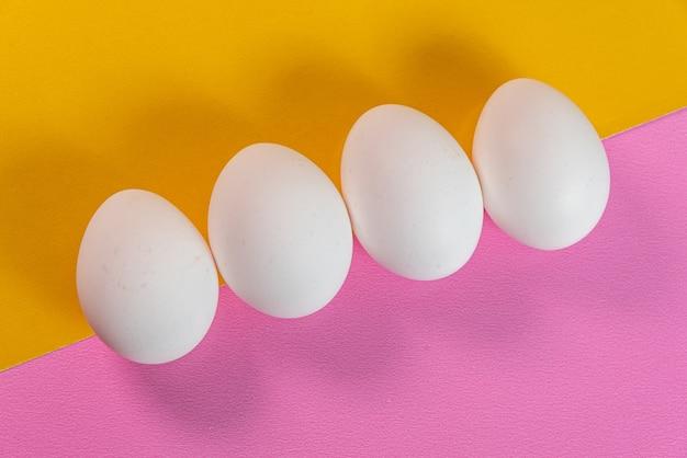 Eier auf der gelben und rosa oberfläche