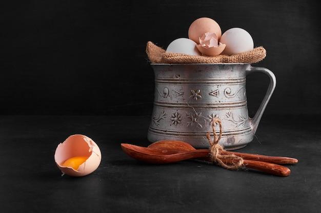 Eier auf einem stück sackleinen in einem metalltopf auf schwarzraum.