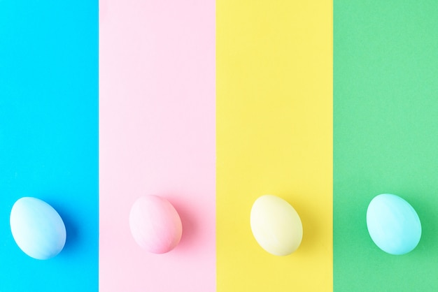 Eier auf farbigem gestreiftem hintergrund, draufsicht, minimalismuskonzept