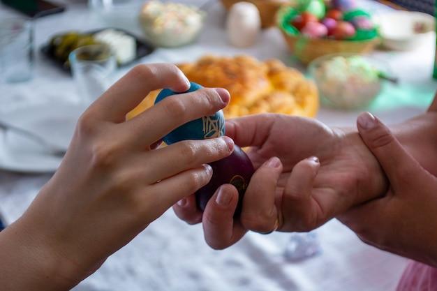 Eier auf ortodoxe ostern mit tisch voller lebensmittel klopfen
