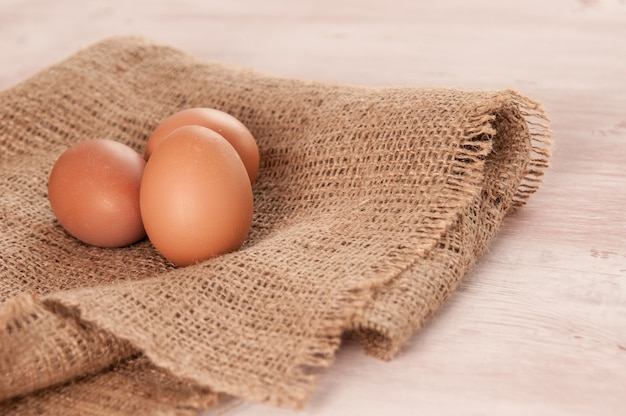 Eier auf sackleinen über hölzernem tischhintergrund