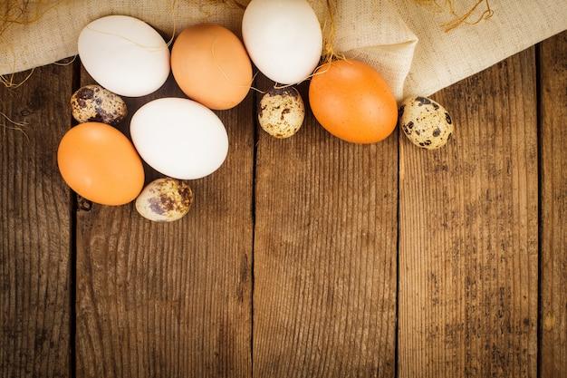 Eier auf textiltischdecke über rustikalem holztisch mit exemplar