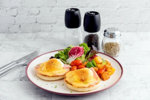 Eier benedict auf englischem muffin mit geräuchertem lachs, salatsalatmischung und sauce hollandaise auf weißem brett