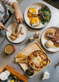 Eier benedict, knuspriger speck gefüllt französischer toast, käsekartoffel mit knusprigem speck und pfannkuchen.