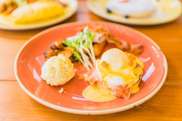 Eier benedict mit geräuchertem lachsspeck und kartoffeln