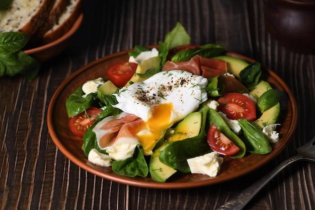 Eier benedict pochierter parmaschinken scheiben von avocado-tomaten und zarten blattspinat gewürzt