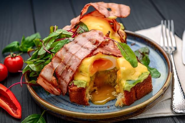 Eier benedikt - geröstet, speck, pochierte eier und köstliche butter-sauce hollandaise. ein restaurant
