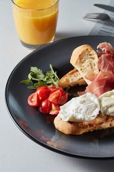Eier benedikt mit brot und tomate, speck, salat auf einem teller