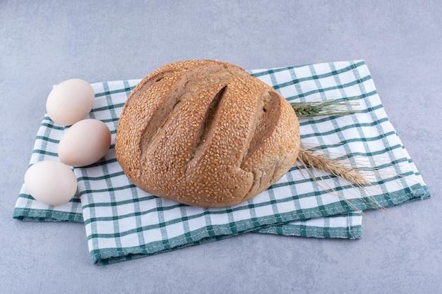 Eier, brotlaib, weizenstiele auf einem gefalteten handtuch auf marmoroberfläche