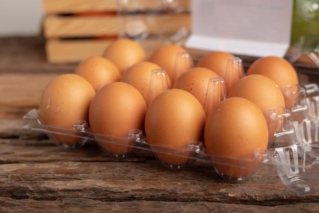 Eier des huhns in einem plastikkasten gesetzt auf einen holztisch