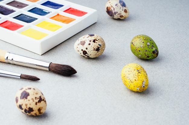Eier färben für ostern. farben, pinsel, wachteleier auf grauem hintergrund. vorbereitung für die feier von ostern, traditionelle dekorationen, hintergrund. kreatives konzept.