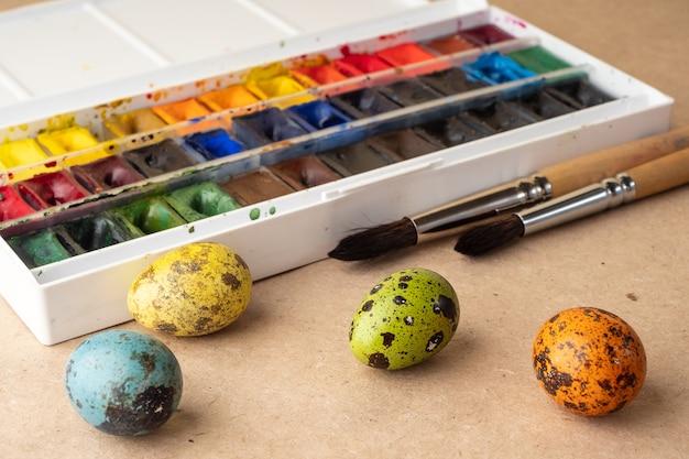 Eier färben für ostern. farben, pinsel, wachteleier auf handwerklichem hintergrund. vorbereitung für die feier von ostern, dekorationen für den urlaub, hintergrund. kreatives konzept.