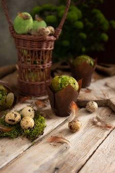 Eier, federn und muffins mit pistazien auf hellem holztisch