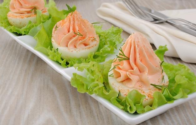 Eier gefüllt mit lachspastete mit paprika in salatblättern