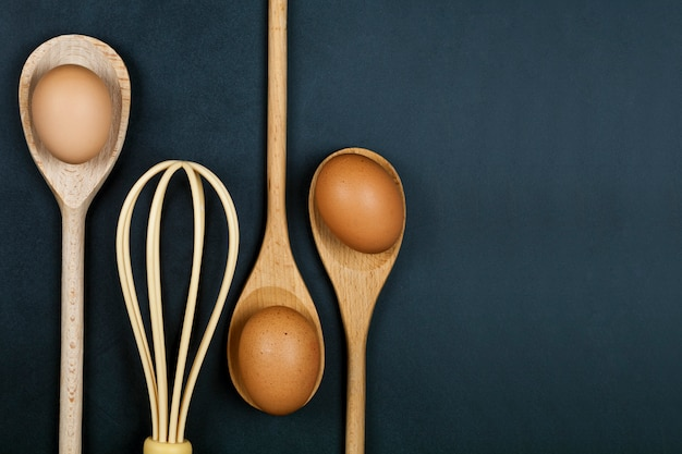 Eier, holzlöffel und schnurrhaar. küchengerät für kuchen, gebäck oder plätzchen auf rückenbretthintergrund.