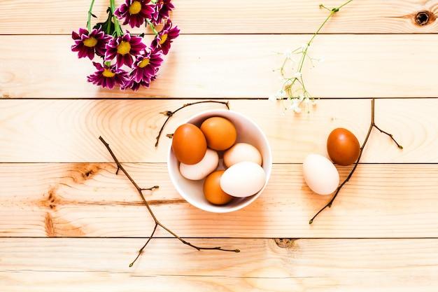 Eier i keramikschale, teller holzhintergrund, vorbereitung ostern, landwirtschaftliche produkte, hühnerei, dekorieren hausurlaub, äste mit knospen, frühling, schöne leuchtend rote blumen, chrysanthemen
