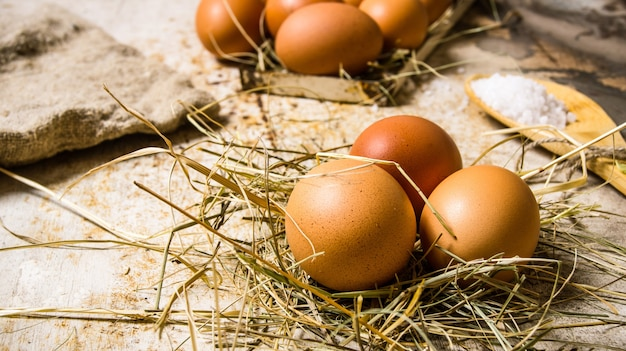 Eier im heu. auf einem rustikalen tisch.