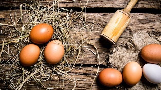 Eier im heu mit einem stößel. auf einem holztisch. draufsicht