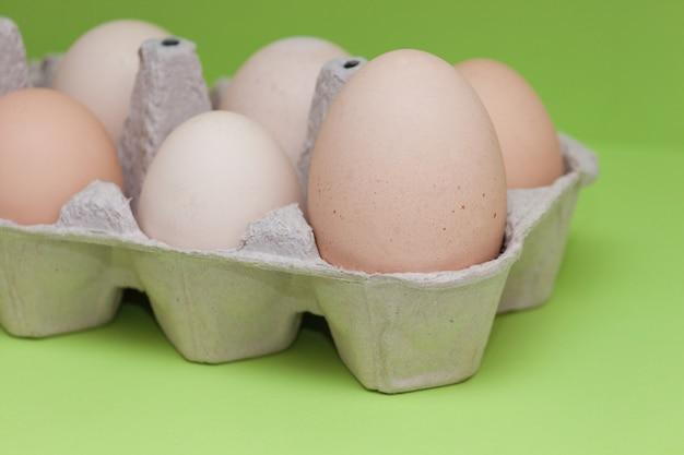Eier im karton, der größte unter anderen kleinen eiern auf dem hellgrünen hintergrund. hauptkonzept, führer, wichtig.