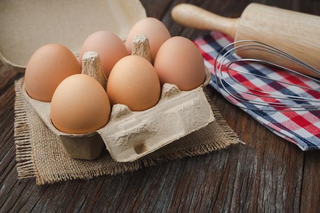 Eier im karton mit schneebesen und nudelholz auf holztisch für koch- und bäckereikonzept