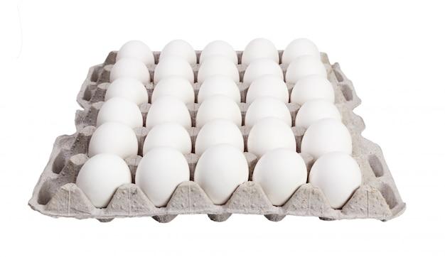Eier im kartonpaket auf weißem hintergrund