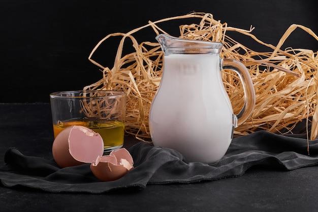 Eier im nest mit einem glas milch auf schwarzem backgorund.