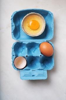 Eier in der blauen eierbox. minimalistisches lebensmittelkonzept. flache lage. draufsicht.