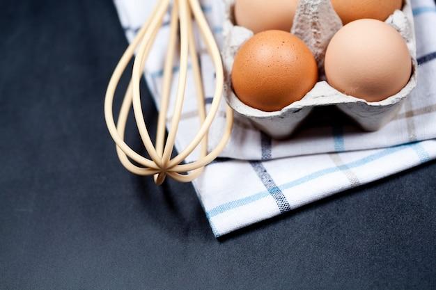 Eier in der pappschachtel-, tuch- und bartnahaufnahme auf rückenbretthintergrund.