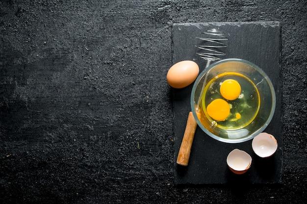 Eier in der schüssel mit schneebesen auf rustikalem tisch